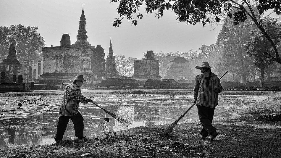 Tuinmannen vegen bladeren, Sukhothai (Thailand)