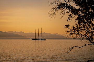 Een boot, zee en berglandschap bij dageraad van Leo Schindzielorz