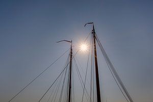 Zonsondergang tussen de masten van twee schepen in.