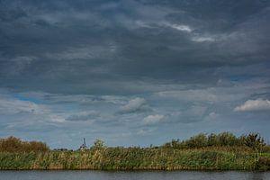 Un paysage néerlandais avec de l'eau, un moulin et des nuages