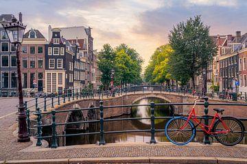 Een rode fiets op de Keizersgracht in Amsterdam van Thea.Photo