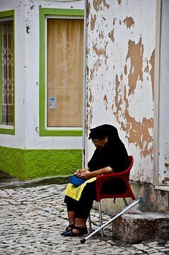 Vrouw zit voor haar huis van Marieke van der Hoek-Vijfvinkel