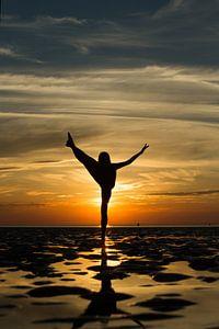 Artistiek naakt op de waddenzee op 1 been in een propeller pose