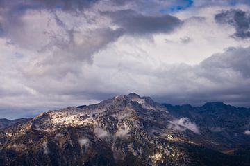 Top van de rotsachtige berg en dreigende wolken. Extreem symbool. van Michael Semenov