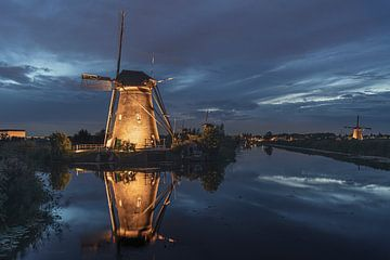 Verlichte windmolen gereflecteerd op het rustige kanaalwater van Digikhmer