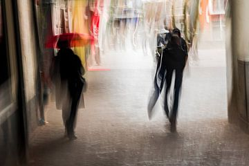 Twee mensen lopen van onder een overkapping de regen in van Jeroen Mank