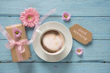 Kaffeetasse, rosa Blumen und ein Geschenk auf pastellblauem Holzgrund mit Kopierfeld, Text Guten Mor von Maren Winter
