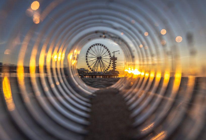 De Pier in Scheveningen gefotografeerd door een lege fles op het strand. van Claudio Duarte