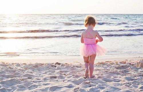 Meisje in roze tutu op het strand