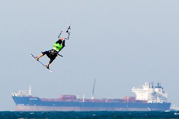 Kitesurfer boven vrachtschip van