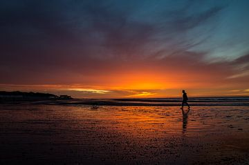Zonsondergang met wandelaar op het strand van