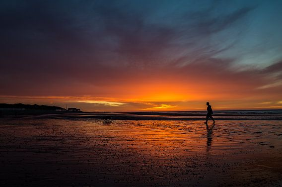 Zonsondergang met wandelaar op het strand