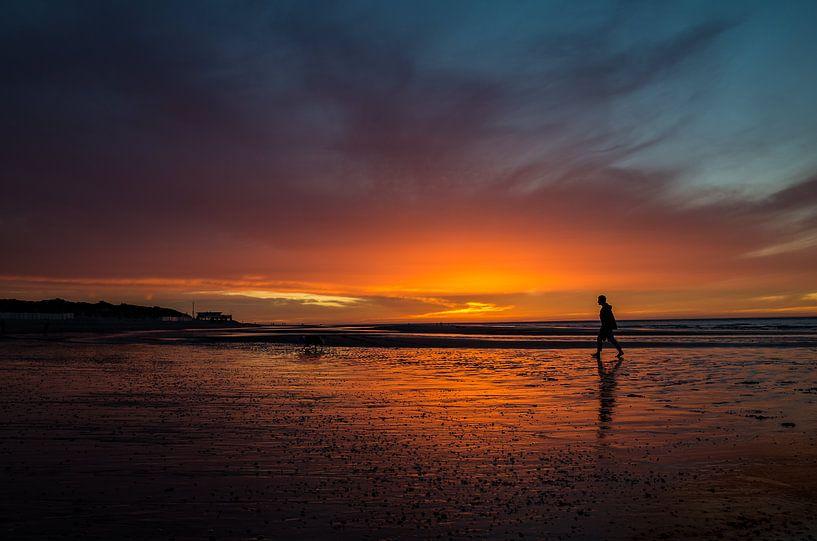 Zonsondergang met wandelaar op het strand van Bart van Dam