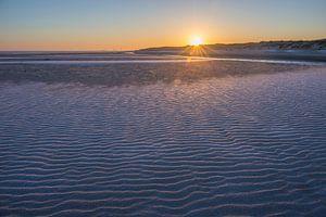 Zonsopkomst aan een winters strand van