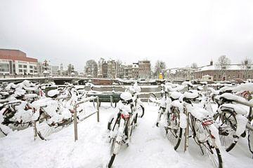 Besneeuwde fietsen in Amsterdam Nederland in de winter van Nisangha Masselink