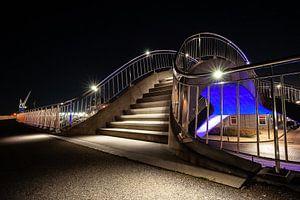 Futuristische verlichte publieke werken met trappen, voetgangerspad en train viaduct