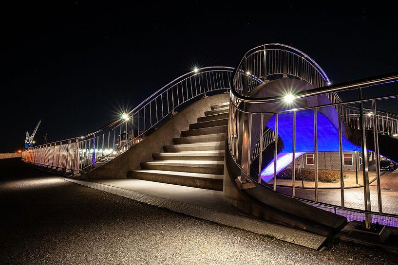 Futuristische verlichte publieke werken met trappen, voetgangerspad en train viaduct van Fotografiecor .nl