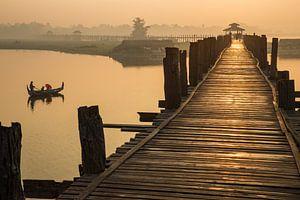 Gondola monte au lever du soleil le long du pont U Mandelay BAIN au Myanmar. Le pont est le plus lon