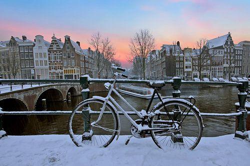 Sunset in snowy Amsterdam in the Netherlands in winter van