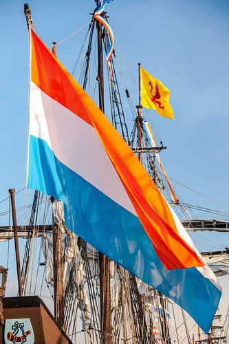 Grote wapperende Nederlandse vlag aan een oud zeilschip