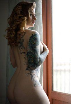 tätowiertes sexy Aktmodell vor einem Fenster