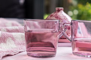 Satz rosa Teegläser mit Flüssigkeit für einen besonders rosa Hintergrund mit einer Vase von Idema Media