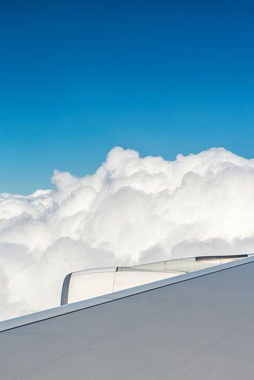 Flugzeugflügel mit Motor und Wolken