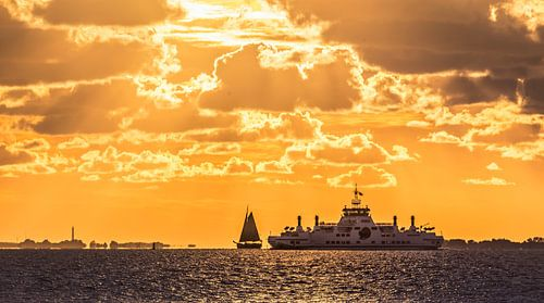 Zonsondergang met zeilboot en veerboot op het Wad van