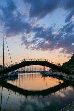 brug bij zonsondergang over water heen met weerspiegeling