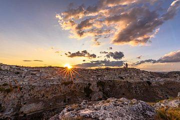 """Matera uit het ravijn bij zonsondergang met zonnestralen over de """"Sassi"""""""