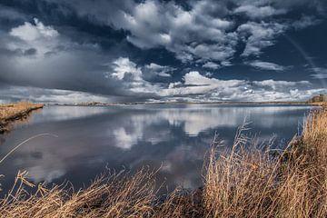 Gespiegelde wolken boven Eeltjemeer/Eeltsjemar omzoomd door een rietkraag. van Harrie Muis
