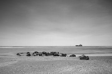 Ameland strand met stenen en vissersboot van Tony Buijse