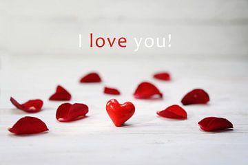 rood glazen hart tussen rozenblaadjes op een lichtgrijze houten achtergrond, tekst Ik hou van je, ge van Maren Winter