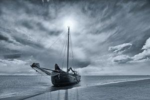 Zwart-wit foto van een drooggevallen zeilschip op een zandbank in de Waddenzee