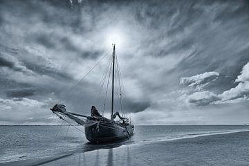 Zwart-wit foto van een drooggevallen zeilschip op een zandbank in de Waddenzee van Bas Meelker