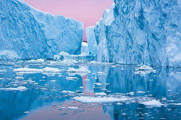 Ijsbergen weerspiegelen onder roze zonsondergang in Groenland van Martijn Smeets