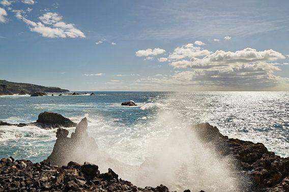 Gischttropfen einer Welle am Steinstrand