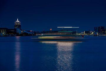 Teil der Skyline von Amsterdam mit Lichtstreifen im Abendlicht von Wim Stolwerk