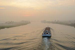 Binnenvaartschip op de rivier de IJssel tijdens zonsopkomst