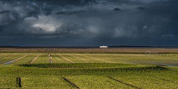 Het Noorderleeg nabij Holwerd met donker weer boven de Wadden. van Harrie Muis