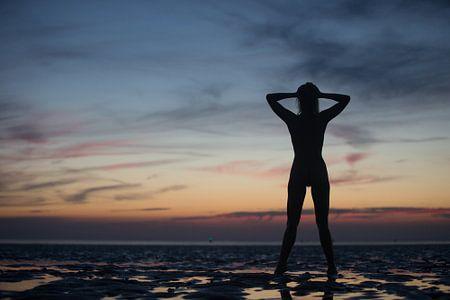 Künstlerische Akt Silhouette mit Sonnenuntergang im Wattenmeer