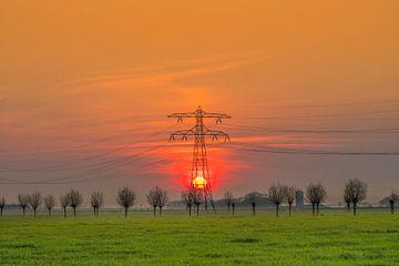 Zonsondergang achter een electriciteitsmast vlak buiten Leeuwarden von Harrie Muis