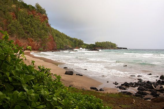 Strand omgeven door rode rotsen