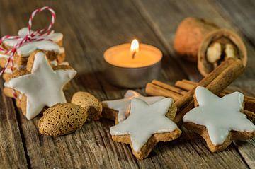 Kerstster koekjes, kaneelkruiden, noten en kaarslicht op houten tafel van Alex Winter