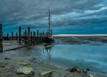 Schip in de haven op drooggevallen wad van Michel Knikker