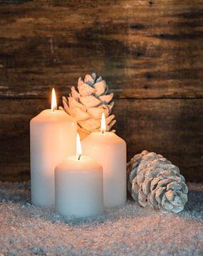 Advent en Kerstmis kaars vlammen met dennenappels decoratie op sneeuw van Alex Winter