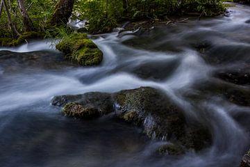 Stromend water met engelenhaar langs de rotsen van Jordi Wallenburg