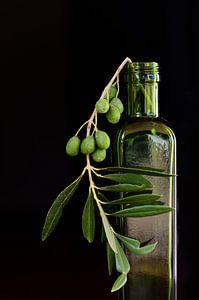 Dans une bouteille verte se trouvent des branches d'olivier
