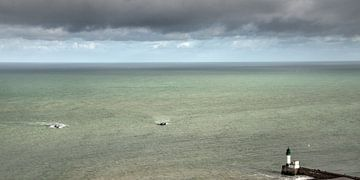 Vissersschepen naderen de pier van