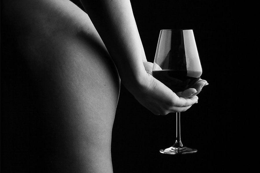 Een foto van een naakte vrouw die een glas wijn vasthoudt achter haar rug.